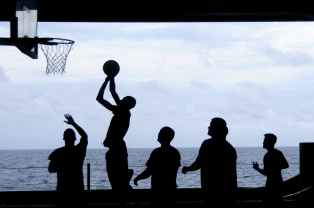 silhouette of men playing basketball
